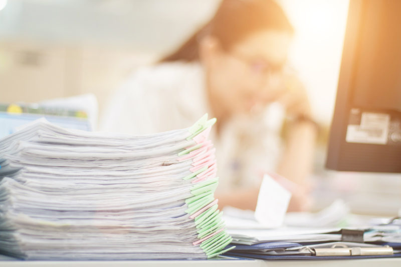 Document work is stacked on many tables. With a blurred image of a woman sitting at work.