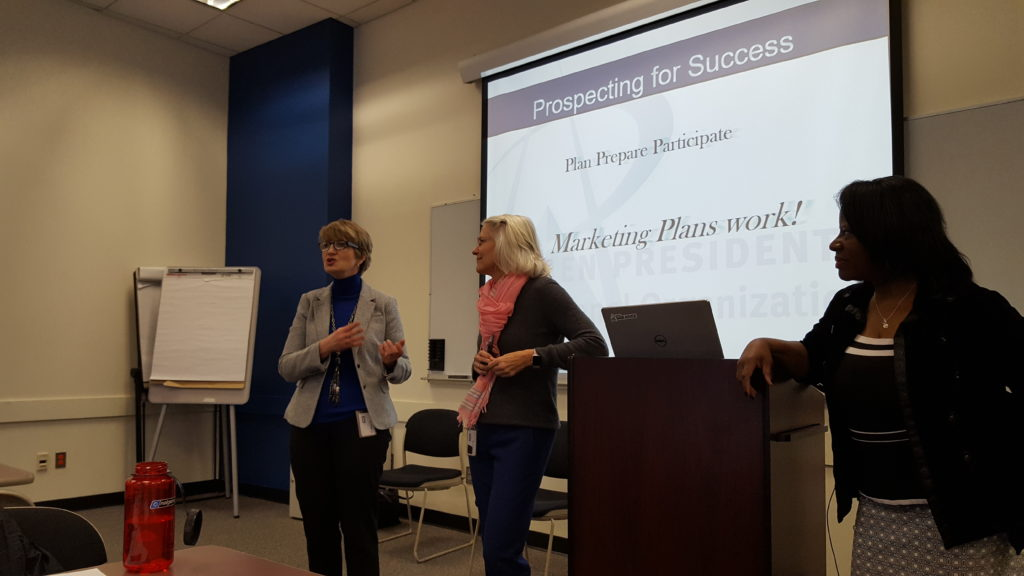 "Three women in front of a presentation that says ""marketing Plans Work''"