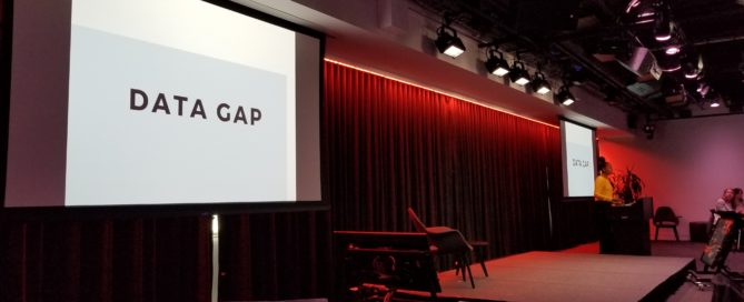 A powerpoint presentation says Data Gap while a woman presents at a podium in the background
