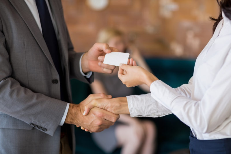 Two professionals exchanging business cards and shaking hands at a restaurant