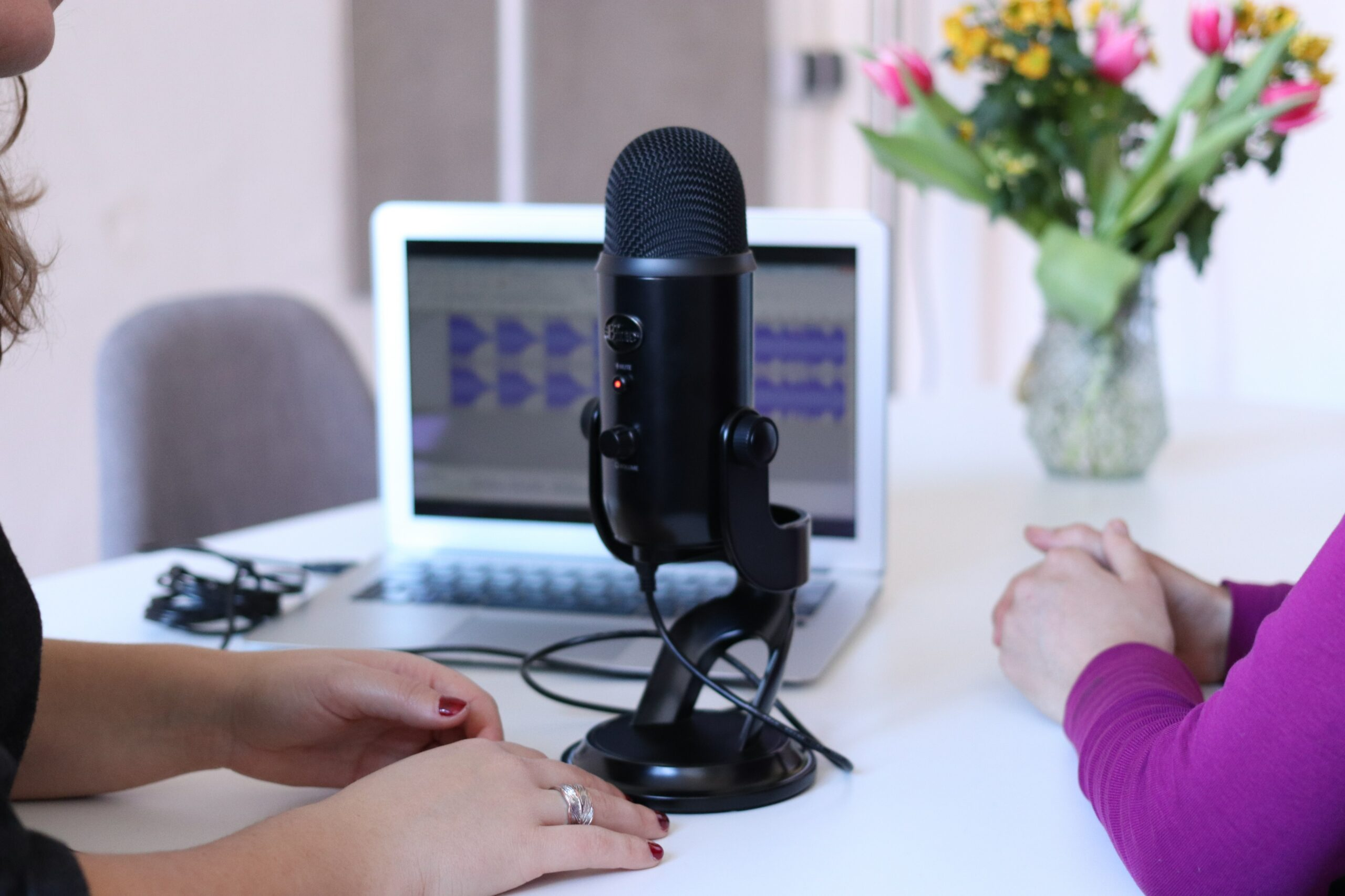 Two women sit around a podcast microphone.