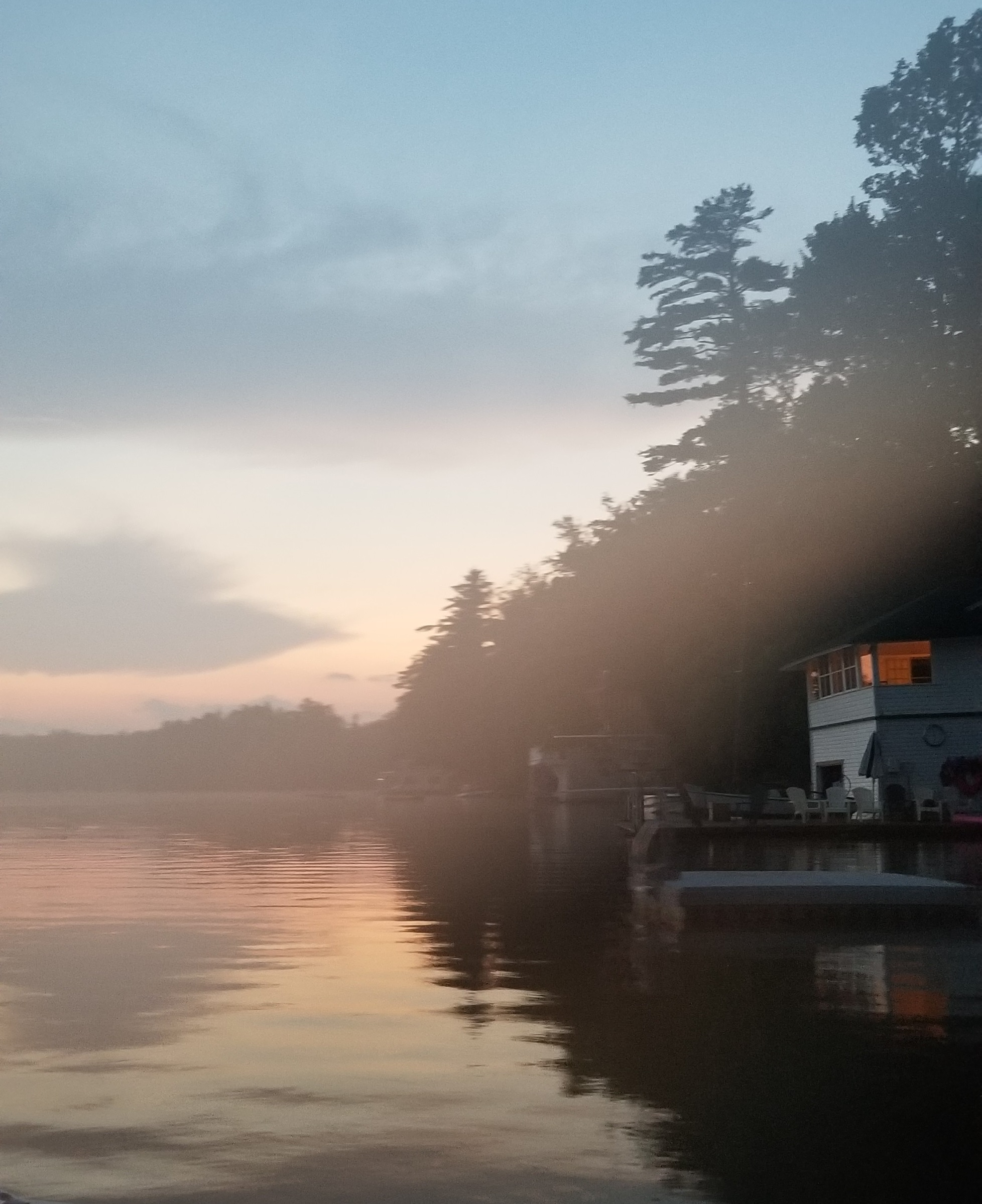View from the water of a boathouse on a lake at dusk