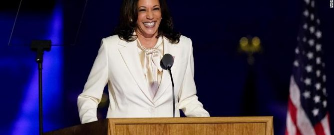 A picture of Kamala Harris VP Elect smiling at a podium